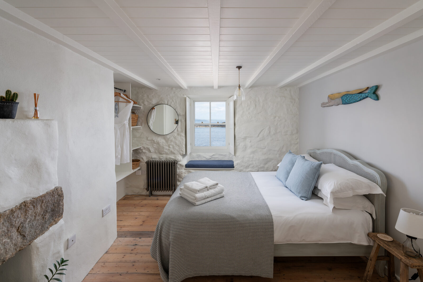The main bedroom has painted stone walls and an original stone fireplace. Pine floorboards run underfoot.