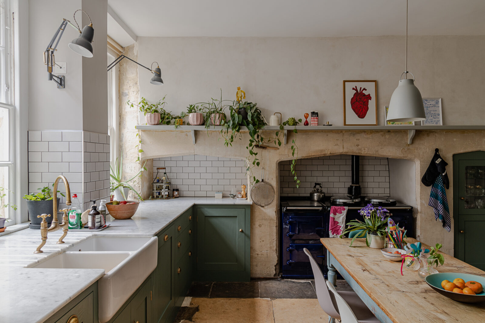 The kitchen has been sensitively updated in keeping with the style of the home: updated cabinets, a double sink and blue aga work effortlessly with stone bath fireplaces