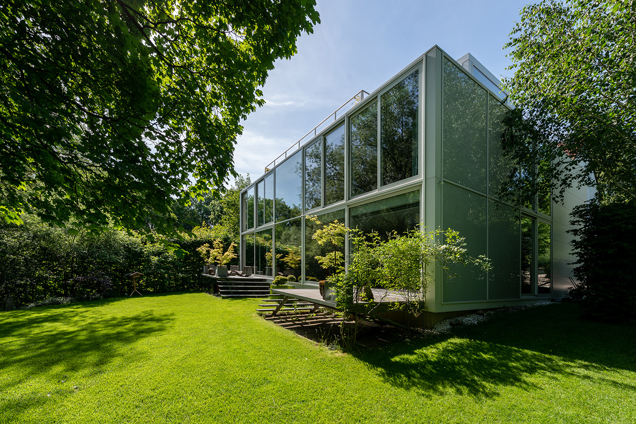 While the front of the building is windowless, at the rear, overlooking the garden, the entire back wall comprises glass panels
