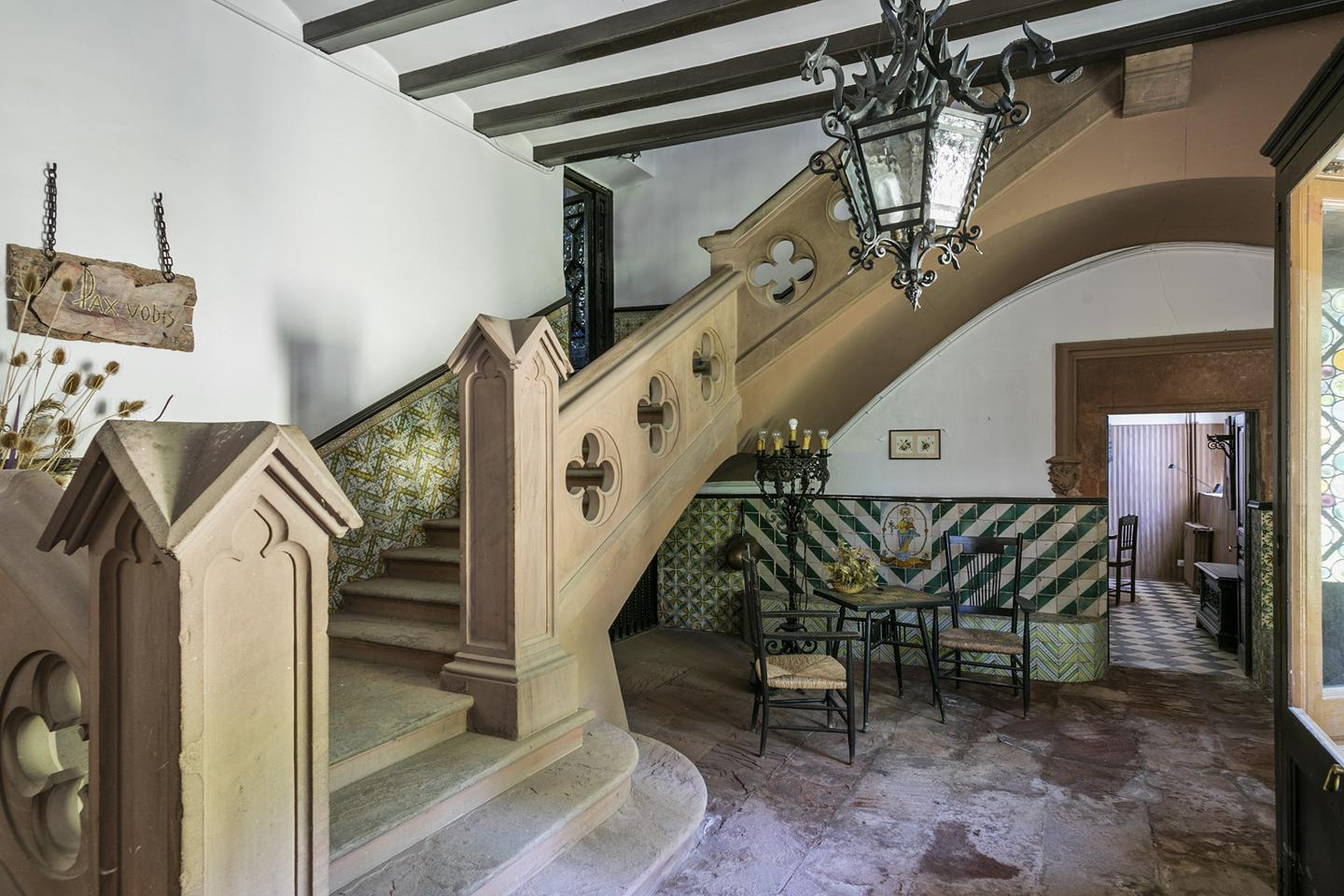 The grand hallway features a carved stone staircase, and an inscribed arch from 1635, while the roof features defensive turrets, which nod to its construction during a chaotic period of history