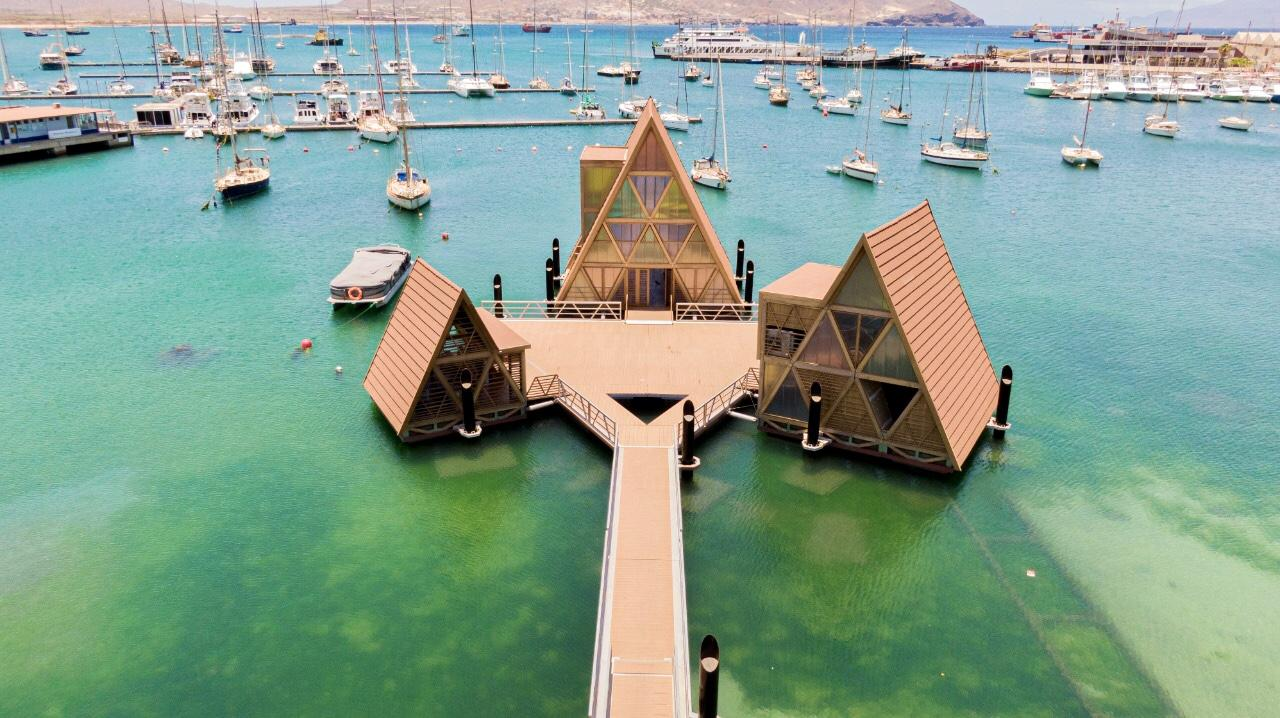 The floating hub features three A frame pavilions connected by a deck and gangway to the shoreline