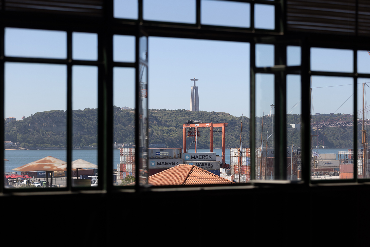 Patinated steel beams cross the space, supported by exposed brickwork while iron-framed windows overlook the Tejo estuary, shipyards beyond, and the city's iconic Santuário de Cristo Rei in Almada.