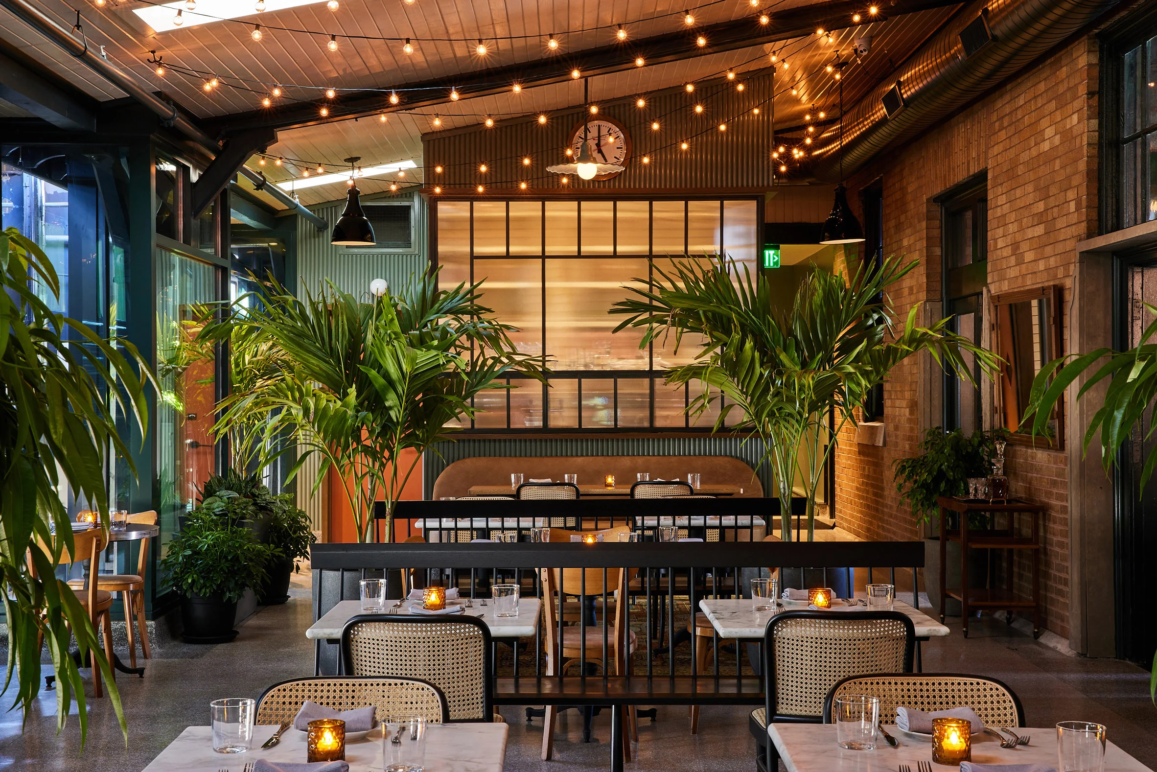 The old train platform is now an informal patio area with string lights and giant palms, and a decommissioned train carriage