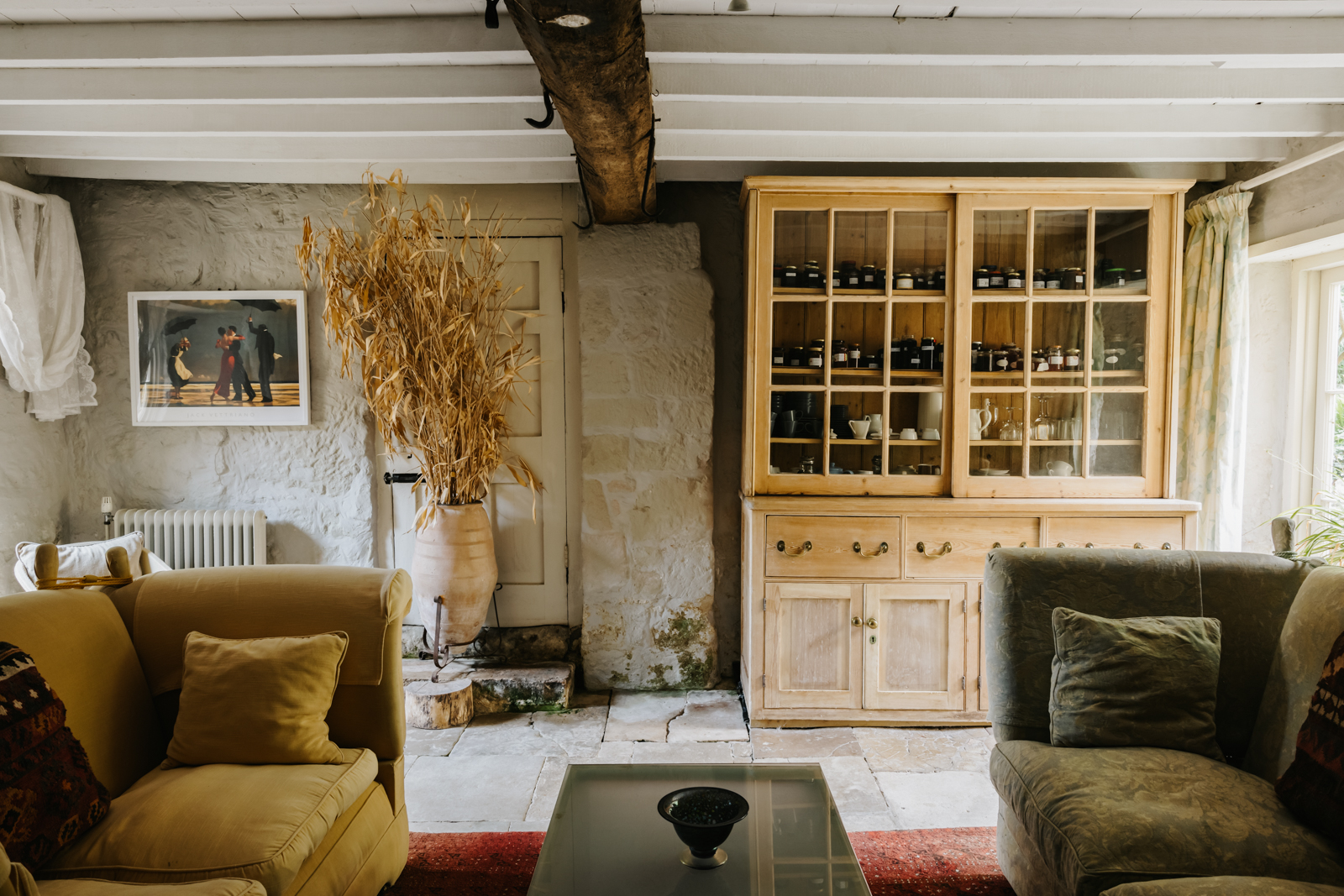 Stone floors and walls, rough hewn beams and raftered ceilings feature in the livingroom