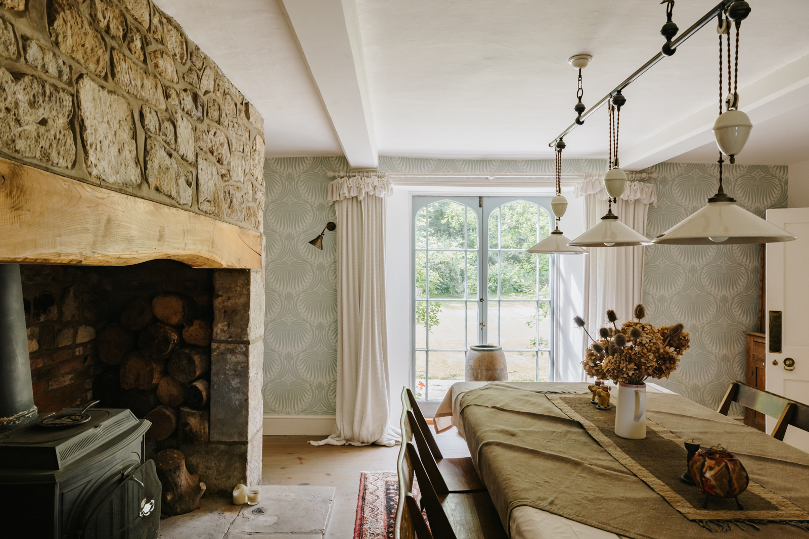 The dining room features french doors that open onto the lawns, as well as a large Inglenook fireplace with woodburning stove