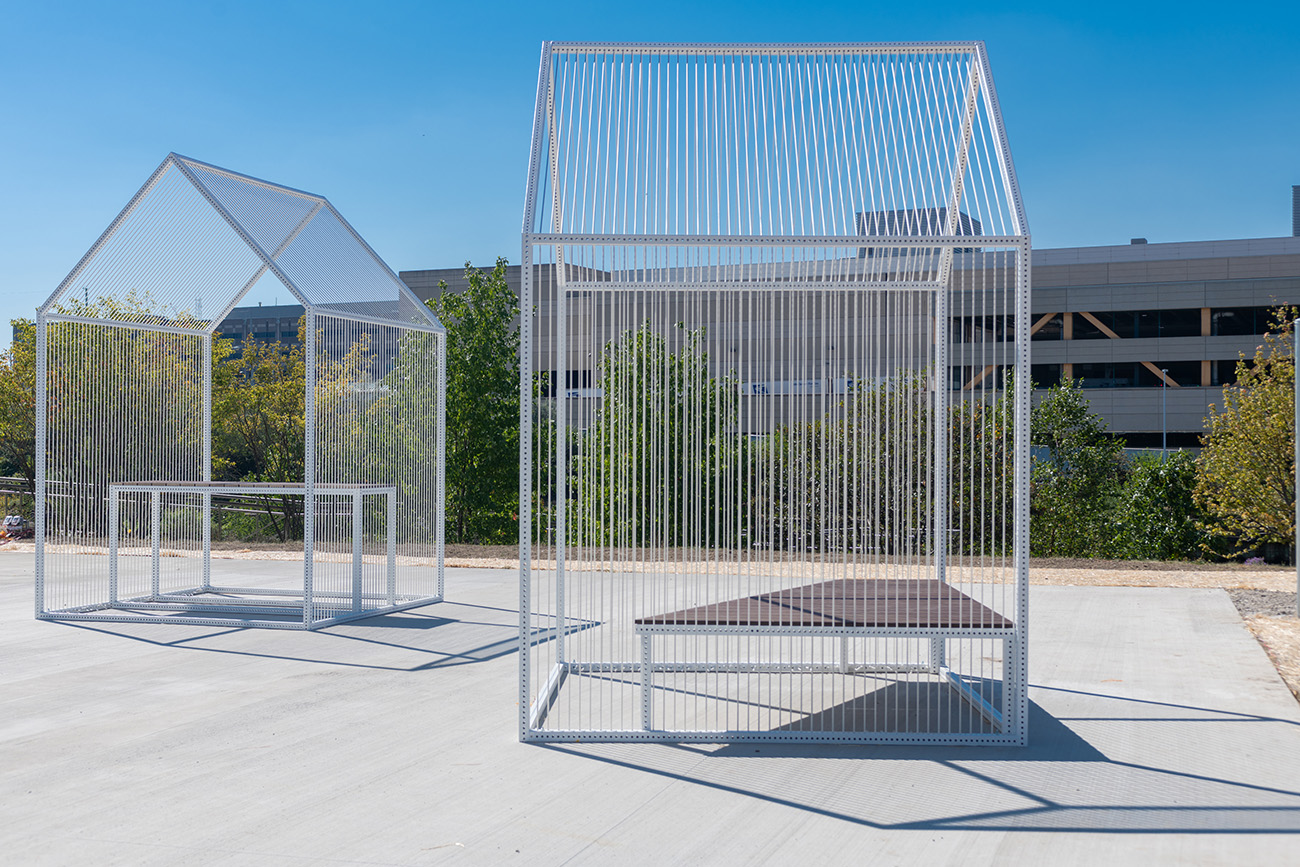 'River frames' are wire-mesh seating pavilions shaped like rudimentary huts