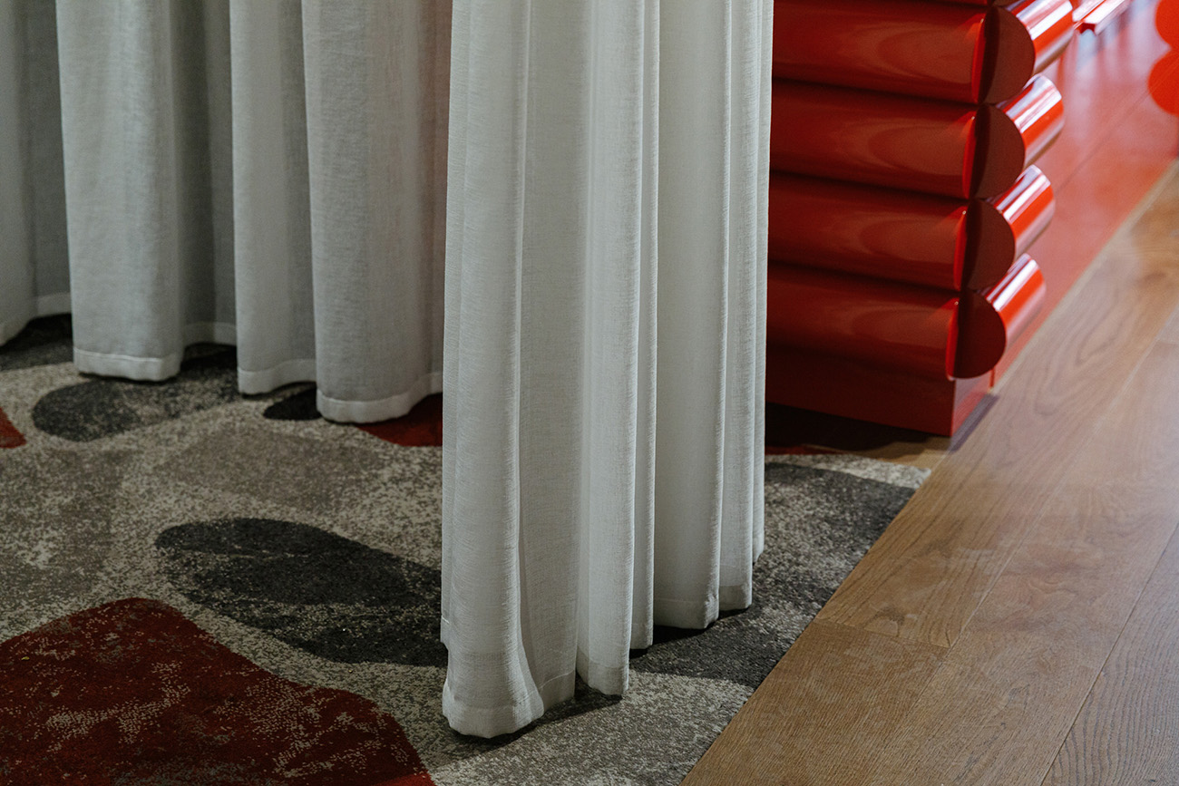 A cross-section of textures: terrazzo-style carpeting, drapes and PoMo cabinetry