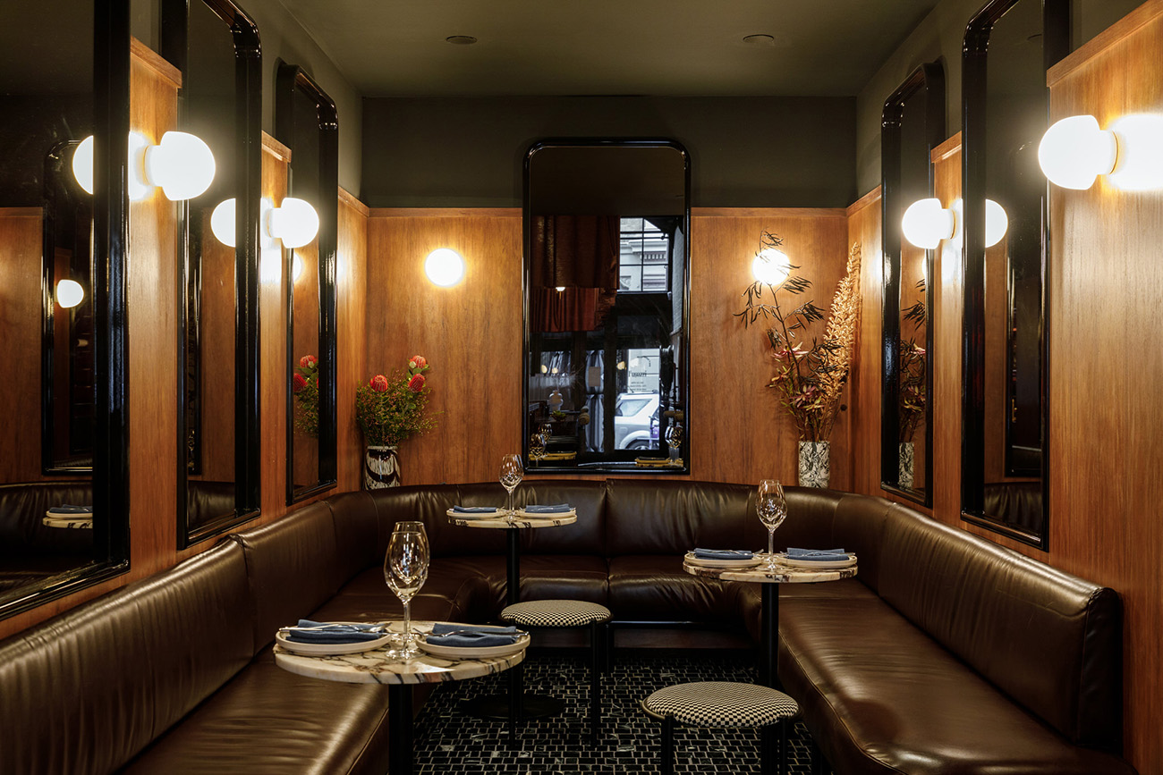 A decadent corner of Fugazzi restaurant feels dark green ceiling accents, timber wall pabels and mirrors, globe lighting and chocolate brown leather banquettes