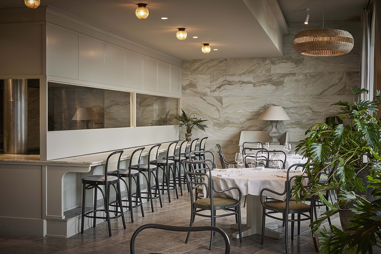 Tactile touches come via cane-backed furniture, simple white tableware, bamboo woven lighting pendants and marble wall cladding