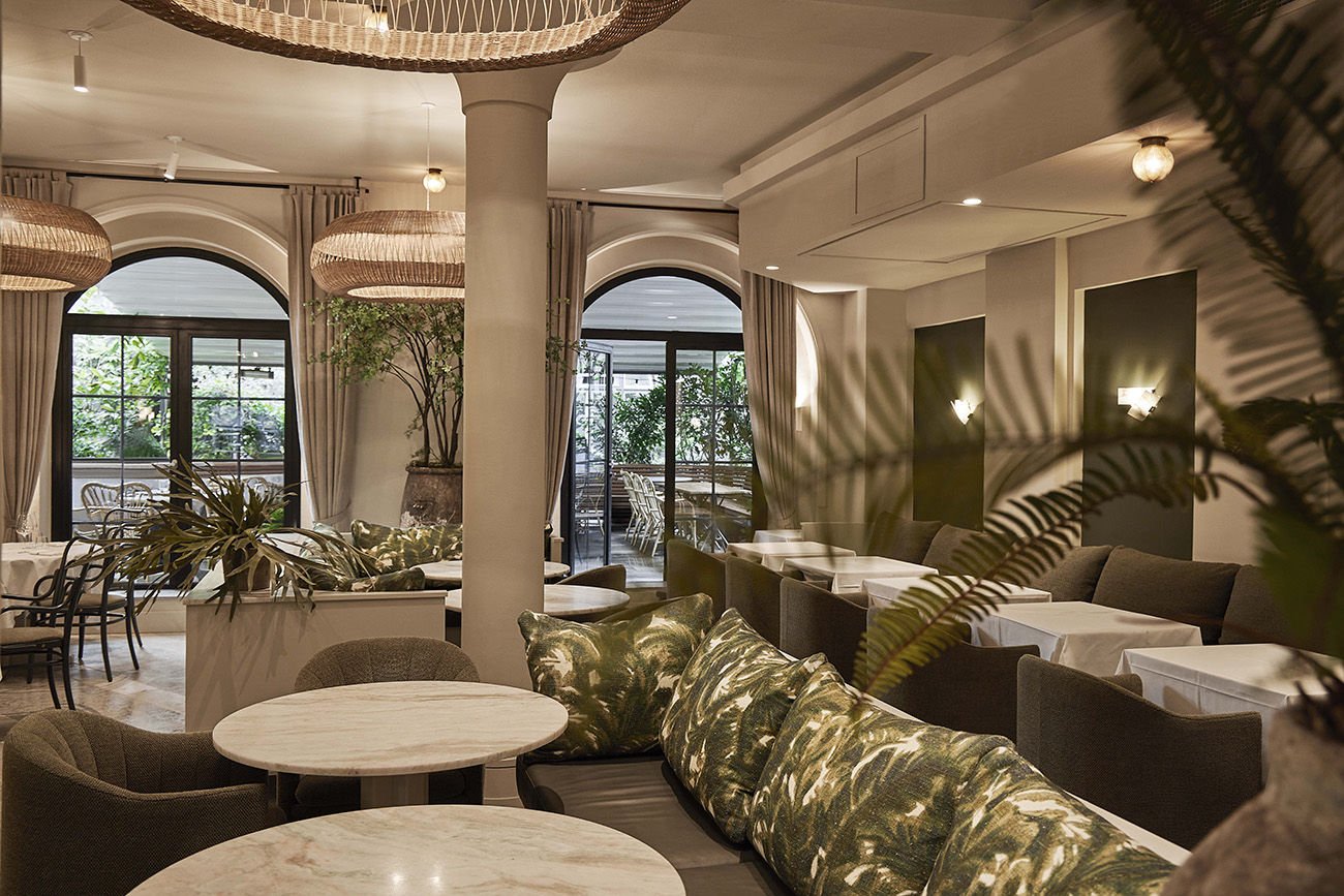 In the galley dining area, seating features botanically-themed upholstery and cushions, ferns and large-leaf evergreen plants