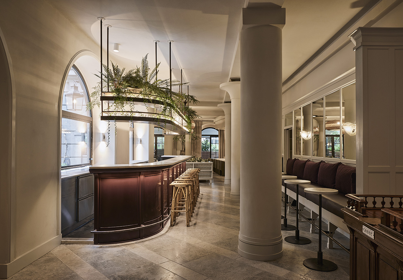 Staggered marble flooring, arched windows and concrete column are the main architectural features of the space
