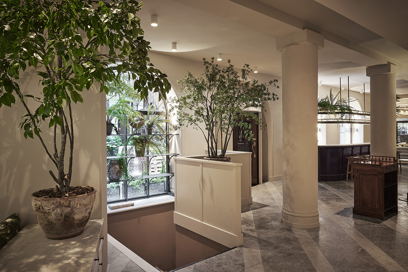Orange trees inject colour into the serene space. The arched windows also feature shelving for potted plants